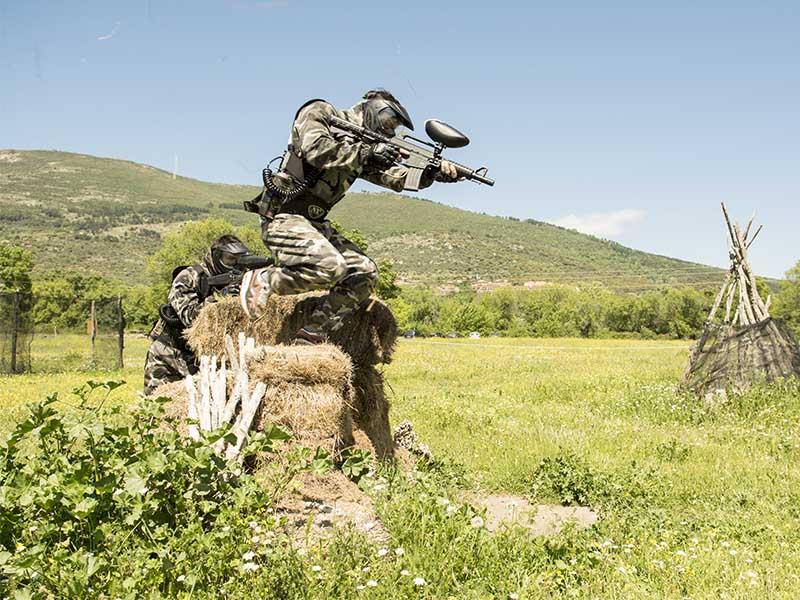 Jugador de paintball saltando por encima de un obstáculo en uno de nuestros campos