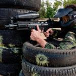 Jugador asomándose por un obstáculo de ruedas disparando al enemigo con una de nuestras mejores marcadoras