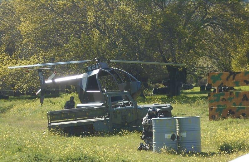 Preciosa foto primaveral de una partida de paintball en madrid en un escenario donde aparece un helicoptero, un coche militar y varios obstaculos