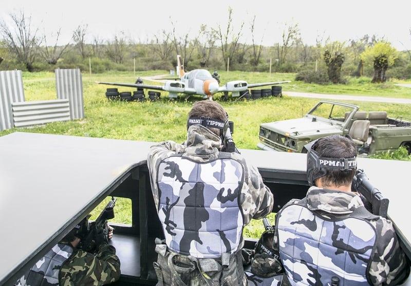 Chicos disparando desde el interior de un tanque del campo de paintball