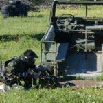 Cliente escondido detrás de un coche militar de uno de los escenarios de los mejores campos de paintball de madrid