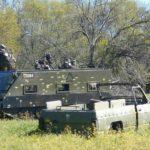 Dos equipos disparándose en Gran Paintball Madrid desde un tanque y un coche militar