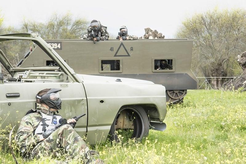 Jugador escondido detrás de un vehículo para que no le vean los jugadores del equipo contrario que están en un tanque