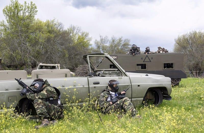 Dors clientes se esconden del enemigo que está en un tanque parapetándose detrás de un vehículo militar