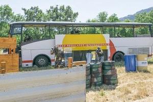Equipo de piantball avanza desde el autobús con un escudo disparando